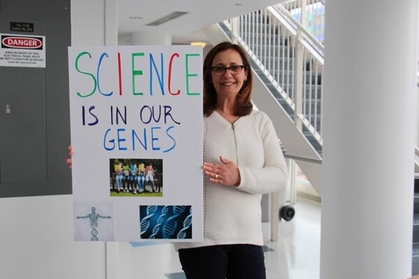 """Woman with """"Science is in our Genes"""" sign"""