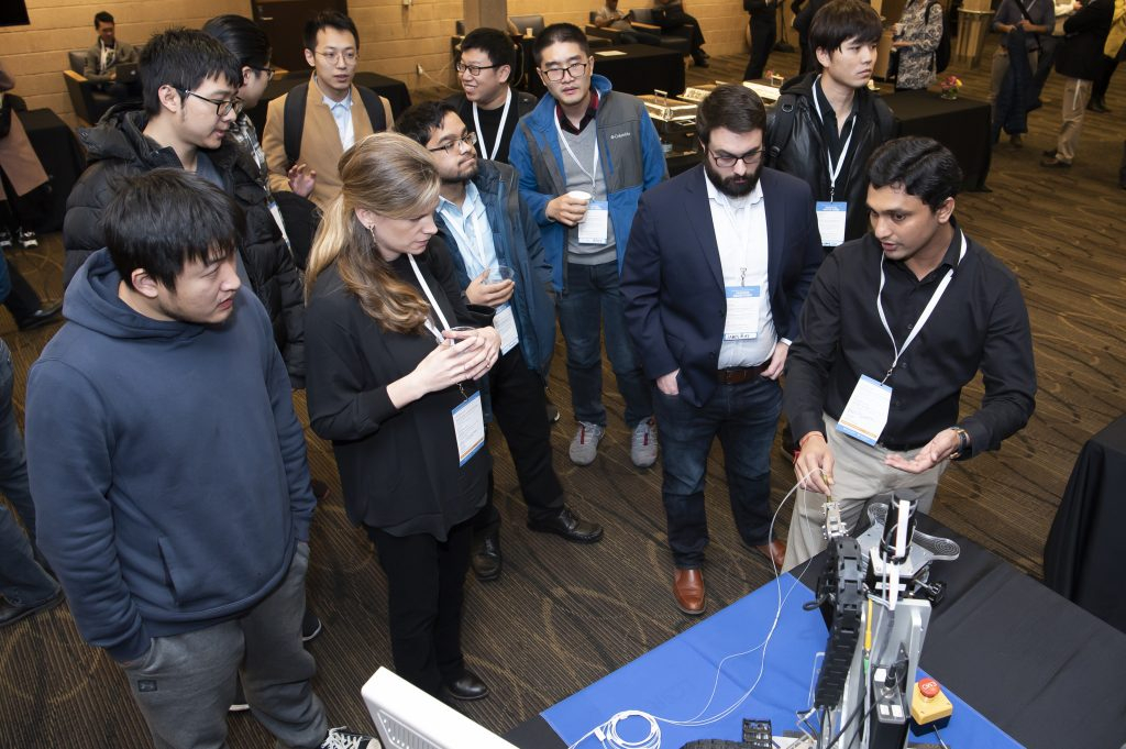 Symposium attendees watch robot demo